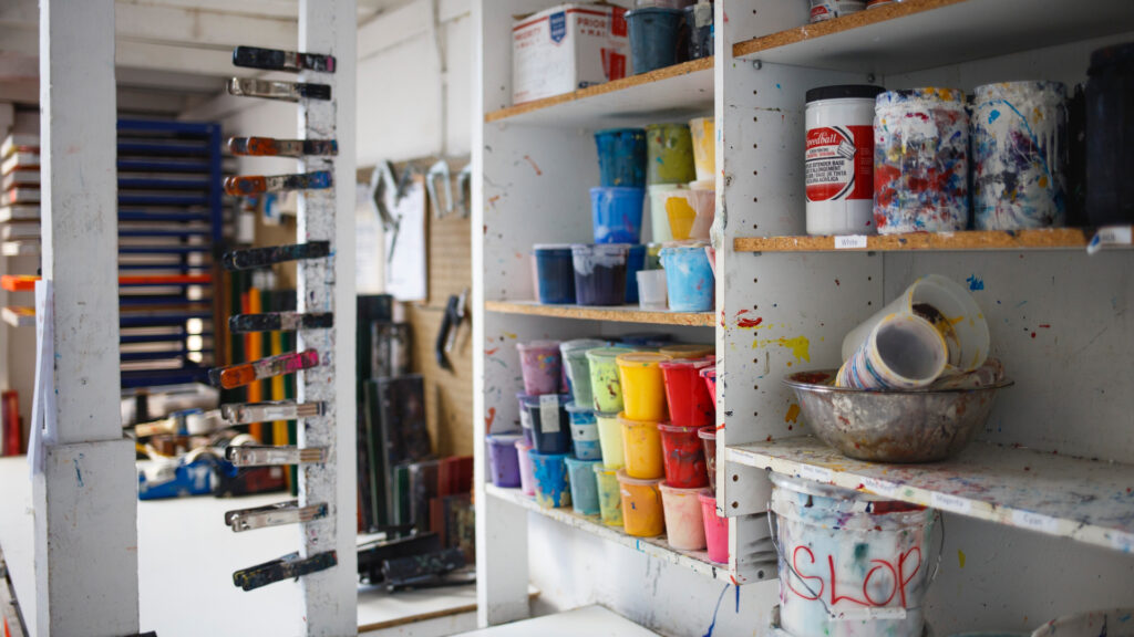 shelves in a home garage filled with ceramic supplies