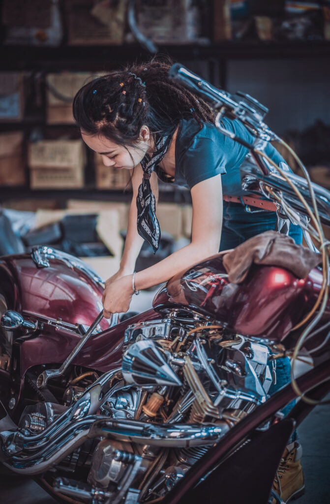 woman tuning up her motorcycle in the garage