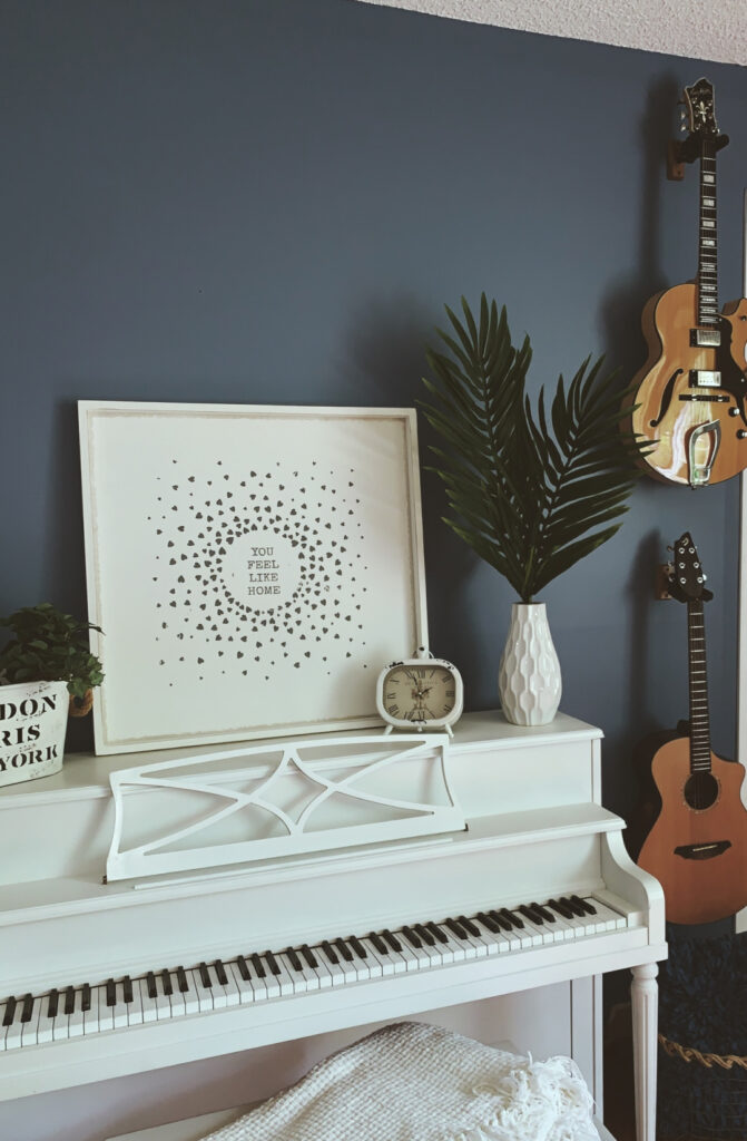 white upright piano and two guitars in a music room